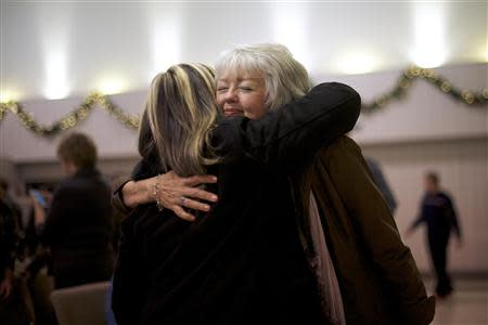 A member of the congregation at New Covenant Community Church embraces Terri Roberts, the mother of Amish school shooter Charles Roberts, in Delta