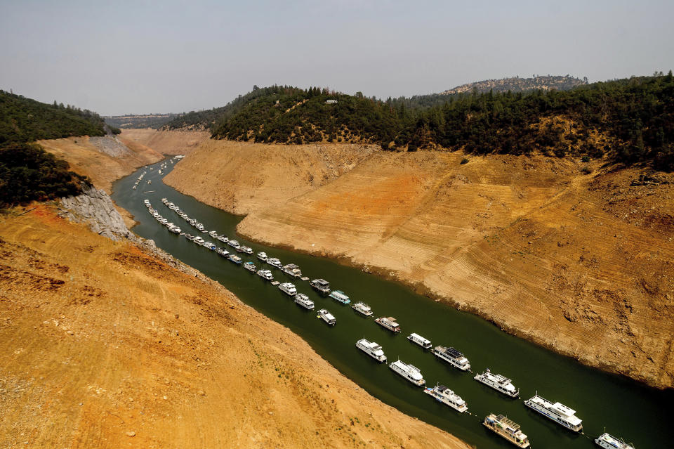 FILE - In this Aug. 14, 2021, file photo, houseboats rest in a channel at Lake Oroville State Recreation Area in Butte County, Calif. At the time of this photo, the reservoir was at 24 percent of capacity and 34 percent of its historical average. A major Southern California water agency has declared a water supply alert for the first time in seven years, Tuesday, Aug. 17, and is asking residents to voluntarily conserve. (AP Photo/Noah Berger, File)