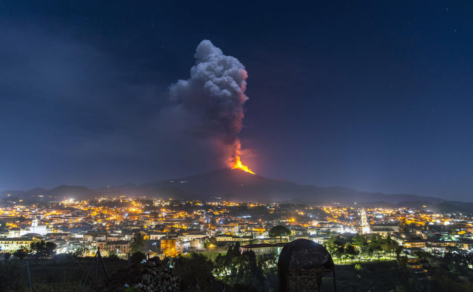 Flames and smoke billowing from a crater, as seen from the southern side of the Mt Etna volcano, tower over the city of Pedara, Sicily, Wednesday night, Feb. 24, 2021. Europe's most active volcano has been steadily erupting since last week, belching smoke, ash, and fountains of red-hot lava. (AP Photo/Salvatore Allegra)