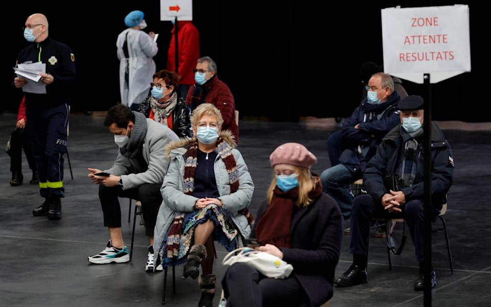 People, wearing protective face masks, wait for their test results at a coronavirus disease (COVID-19) testing center installed inside in the Kursaal concert hall in Dunkirk, France - PASCAL ROSSIGNOL /REUTERS