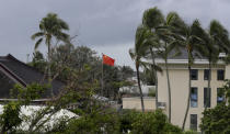 In this April 8, 2019, photo, a Chinese flag flies outside the Chinese Embassy in Nuku'alofa, Tonga. China is pouring billions of dollars in aid and low-interest loans into the South Pacific, and even in the far-flung kingdom of Tonga there are signs that a battle for power and influence among much larger nations is heating up and could exact a toll. (AP Photo/Mark Baker)