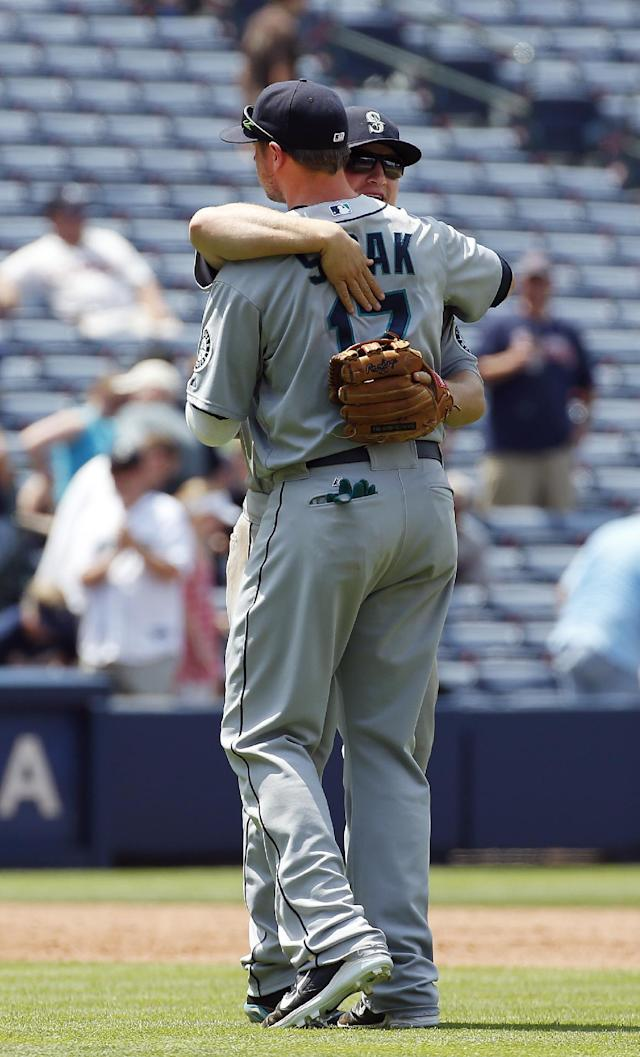 Seattle Mariners third baseman Kyle Seager (15) and first baseman Justin Smoak (17) embrace after defeating the Atlanta Braves 2-0 in a baseball game Wednesday, June 4, 2014 in Atlanta. (AP Photo/John Bazemore)
