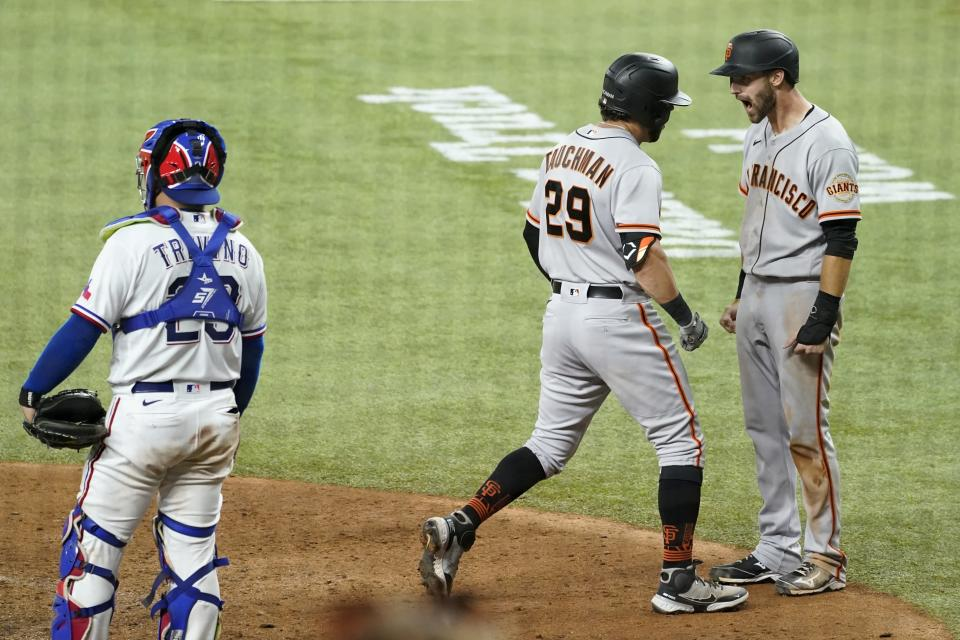 Texas Rangers catcher Jose Trevino (23) stands at the plate as San Francisco Giants' Mike Tauchman (29) and Steven Duggar, right, celebrate Tauchman's grand slam in the eighth inning of a baseball game in Arlington, Texas, Tuesday, June 8, 2021. (AP Photo/Tony Gutierrez)
