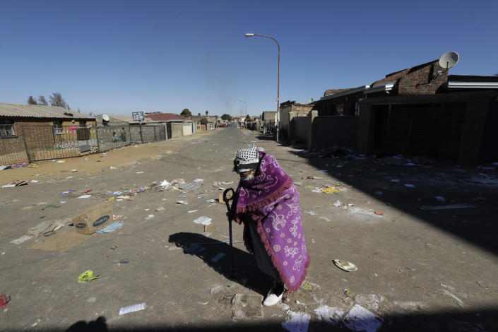 An elderly woman crosses a littered street caused by looters in Soweto near Johannesburg, Tuesday July 13, 2021 as ongoing looting and violence continues. South Africa's rioting continued Tuesday with the death toll rising to 32 as police and the military struggle to quell the violence in Gauteng and KwaZulu-Natal provinces. The violence started in various parts of KwaZulu-Natal last week when Zuma began serving a 15-month sentence for contempt of court. (AP Photo/Themba Hadebe)