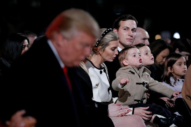 <p>White House senior advisor Jared Kushner, seated with his wife White House senior advisor Ivanka Trump and their children, looks over at U.S. President Donald Trump as he bows his head during the prayer at the National Christmas Tree lighting ceremony near the White House in Washington, Nov. 30, 2017. (Photo: Jonathan Ernst/Reuters) </p>