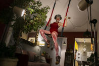 """Trapeze artist Regina Oliveira performs her clown act for live, online streaming of the """"Benditas Genis"""" women's clown festival at her home during the COVID-19 pandemic in Rio de Janeiro, Brazil, Sunday, March 14, 2021. Oliveira transformed her apartment in the hilltop Santa Teresa neighborhood into a small studio, complete with professional lighting and trapeze, to give classes and presentations. (AP Photo/Bruna Prado)"""