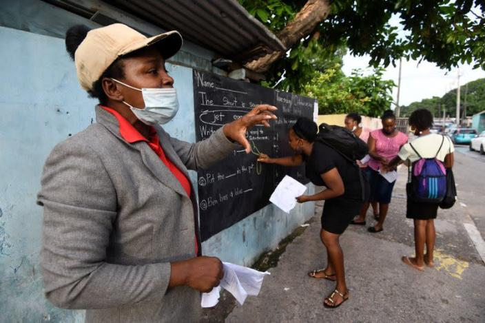 Educator Mckoy Phipps teaches a lesson next to a blackboard painted on a wall during the coronavirus disease (COVID-19) outbreak in Kingston