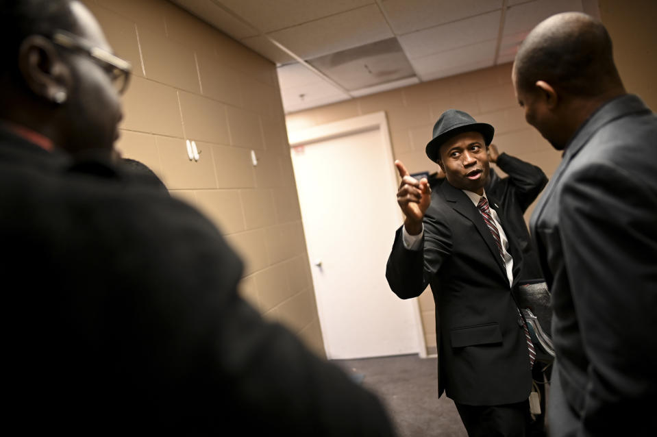 Erik Anderson, left, of Trenton, N.J., is greeted by Brooklyn Center Mayor-elect Mike Elliott, center, before Elliot's inauguration ceremony, Wednesday, Jan. 2, 2019, at the Brooklyn Center Community Center, in Brooklyn Center, Minn. Elliott is the city's first Black and first Liberian American mayor. Elliott, who emigrated from Liberia as a child, is finding just how difficult it is to turn the page on the nation's racial history as he handles the fallout from a police shooting. (Aaron Lavinsky/Star Tribune via AP)