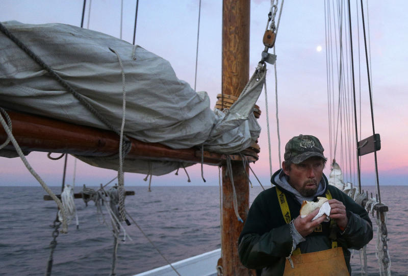 In this Dec. 20, 2013 picture, Danny Benton eats breakfast before a day of oyster dredging aboard the skipjack Hilda M. Willing in Tangier Sound near Deal Island, Md. (AP Photo/Patrick Semansky)