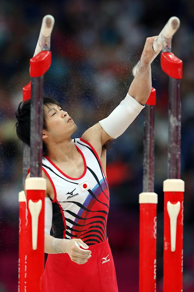 LONDON, ENGLAND - JULY 30: Kohei Uchimura of Japan puts chalk on the parallel bars in the Artistic Gymnastics Men's Team final on Day 3 of the London 2012 Olympic Games at North Greenwich Arena on July 30, 2012 in London, England. (Photo by Streeter Lecka/Getty Images)
