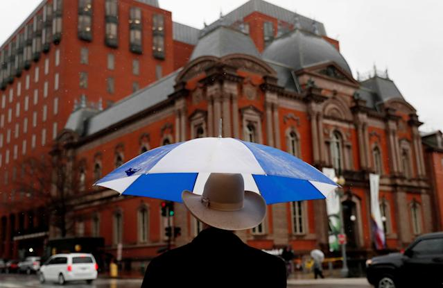 A pedestrian keeps himself dry while waiting to cross the street in Washington, U.S., March 20, 2018. REUTERS/Leah Millis TPX IMAGES OF THE DAY