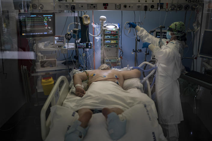 A COVID-19 patient receives treatment in the ICU of the Hospital del Mar, in Barcelona, Spain, Tuesday, Jan. 19, 2021. The unrelenting increase in COVID-19 infections in Spain following the holiday season is again straining hospitals, threatening the mental health of doctors and nurses who have been at the forefront of the pandemic for nearly a year. (AP Photo/Felipe Dana)