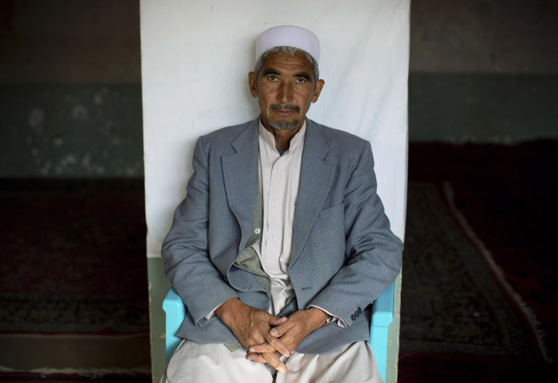 In this Sunday, Nov. 10, 2013 photo, Haji Saher, 55, has his picture taken to register for the upcoming Afghan elections in a mosque, used as a mobile voter registration place in Kabul, Afghanistan. Afghanistan's next president has a tough job, expected to steer his country through a critical transition from war to peace. (AP Photo/Anja Niedringhaus)