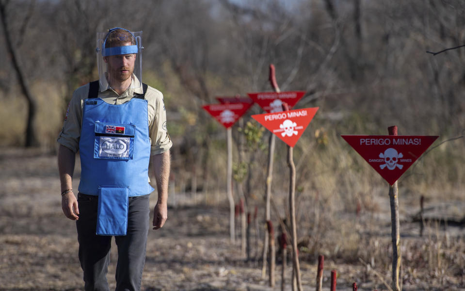 Britain's Prince Harry walks through a minefield in Dirico, Angola Friday Sept. 27, 2019, during a visit to see the work of landmine clearance charity the Halo Trust, on day five of the royal tour of Africa. Prince Harry is following in the footsteps of his late mother, Princess Diana, whose walk through an active mine field in Angola years ago helped to lead to a global ban on the deadly weapons. (Dominic Lipinski/Pool via AP)