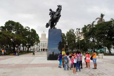 A school teacher explains about the bronze replica of a New York statue of Cuban independence hero Jose Marti after it's unveiling in the historic centre of Havana, Cuba