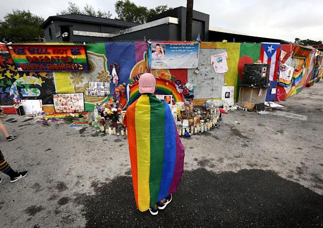 <p>A runner donning a gay pride flag pauses in front of the Pulse nightclub during the CommUNITYRainbowRun 4.9K road race, on Saturday, June 10, 2017, in Orlando, Fla. (Joe Burbank/Orlando Sentinel/TNS via Getty Images) </p>