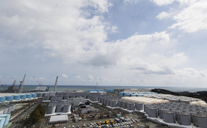 This photo shows tanks (in gray, beige and blue) of storing water that was treated but still radioactive after it was used to cool down spent fuel at the Fukushima Daiichi nuclear power plant in Okuma town, Fukushima prefecture, northeastern Japan, Saturday, Feb. 27, 2021. The reactors of the Unit 3, lower left, and 4 are seen by the ocean. (AP Photo/Hiro Komae)