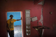 """Orlando Perdomo, 56, stands for a portrait in his home damaged by a landslide triggered by hurricanes Eta and Iota, in the village of La Reina, Honduras, Sunday, June 20, 2021. """"When the first cracks in the earth opened after Hurricane Mitch in 1998, my father said he wouldn't live to see it, but that we would see the town disappear, that the future would bring death,"""" Perdomo recalls. (AP Photo/Rodrigo Abd)"""