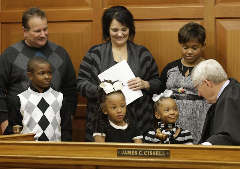 "Judge James Cissell, right, talks with twin sisters Lauriana and Laylah, 5, after they were adopted by Greg Smith, top left, and his wife Robin Smith, top center, along with their brother Laurence, 8, front left, and sister Liasia, 12, top right, Friday, Nov. 22, 2013, in Cincinnati. The Smiths adopted all four siblings to keep them together as a family. They have cared them as foster children for over three years. Robin Smith acknowledged some anger and other issues among the children, stemming from their experiences before coming to the Smiths. ""But you just can't give up on children, not matter how hard the situation is,"" she said. (AP Photo/Al Behrman)"