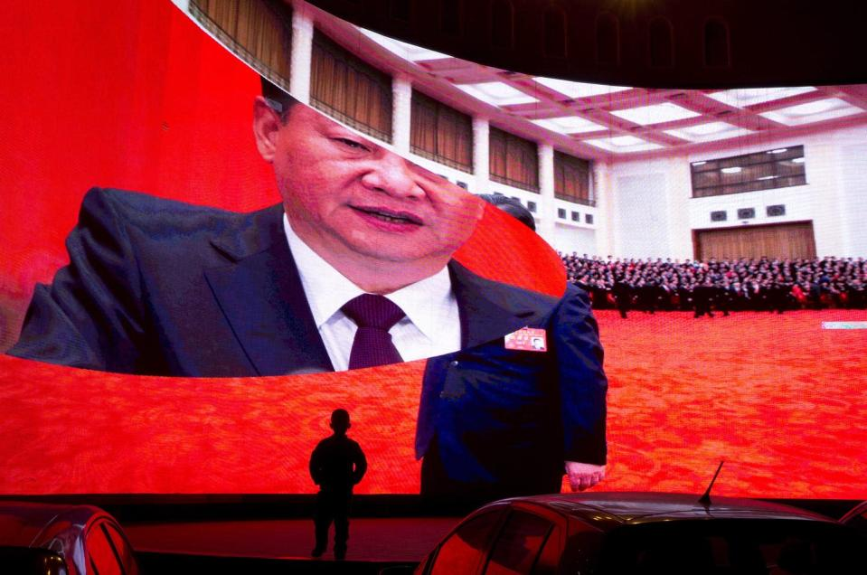 """<span class=""""caption"""">A child stands near a large screen showing photos of Chinese President Xi Jinping near a carpark in Kashgar in western China's Xinjiang region. </span> <span class=""""attribution""""><span class=""""source"""">(AP Photo/Ng Han Guan)</span></span>"""