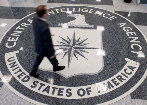 A man crosses the Central Intelligence Agency (CIA) logo in the lobby of CIA Headquarters in Langley