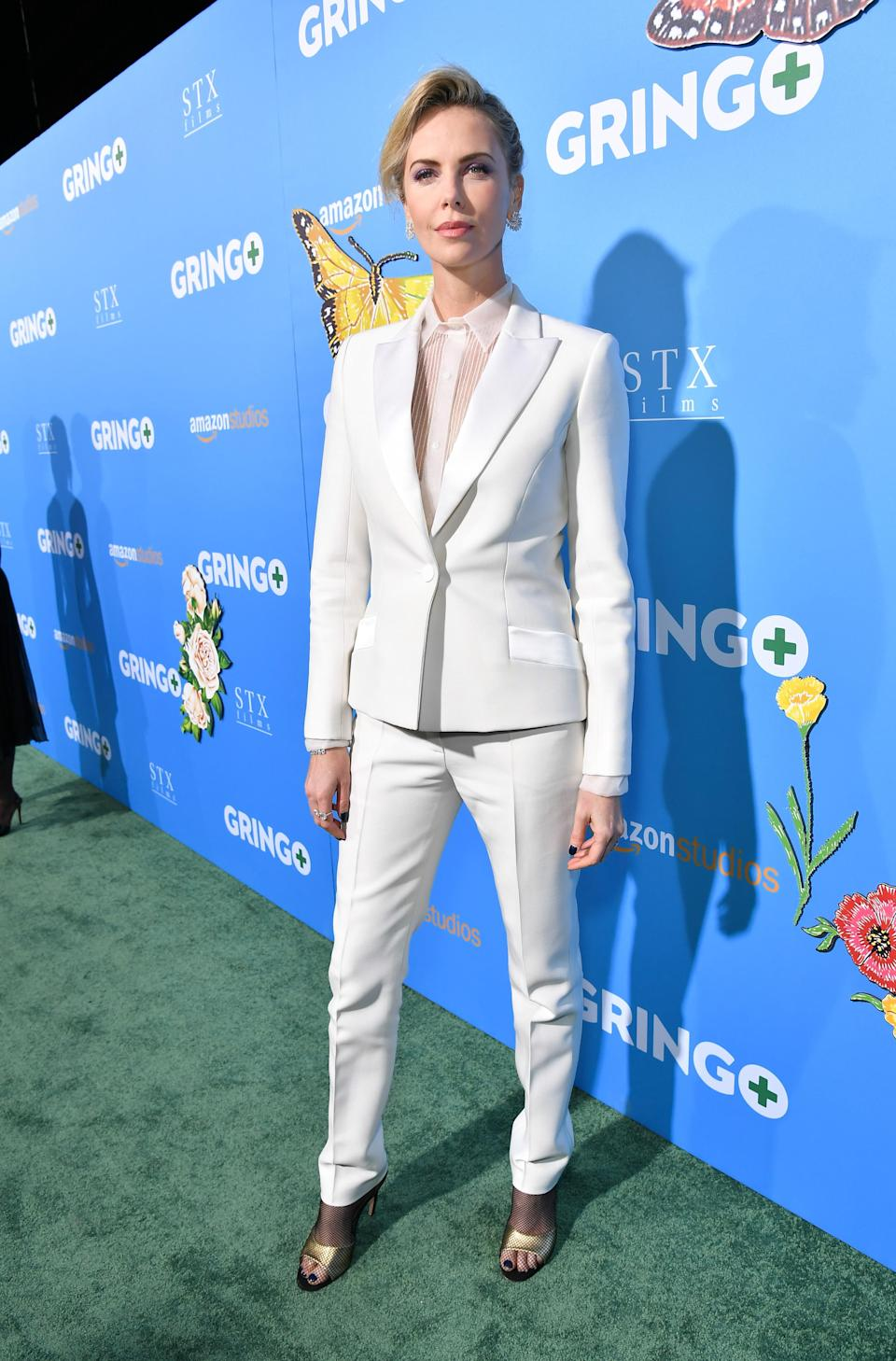 <p>Tuxedoes are a super-stylist red carpet alternative to a classic gown, and Charlize chose well with this all-white ensemble (Rex features) </p>