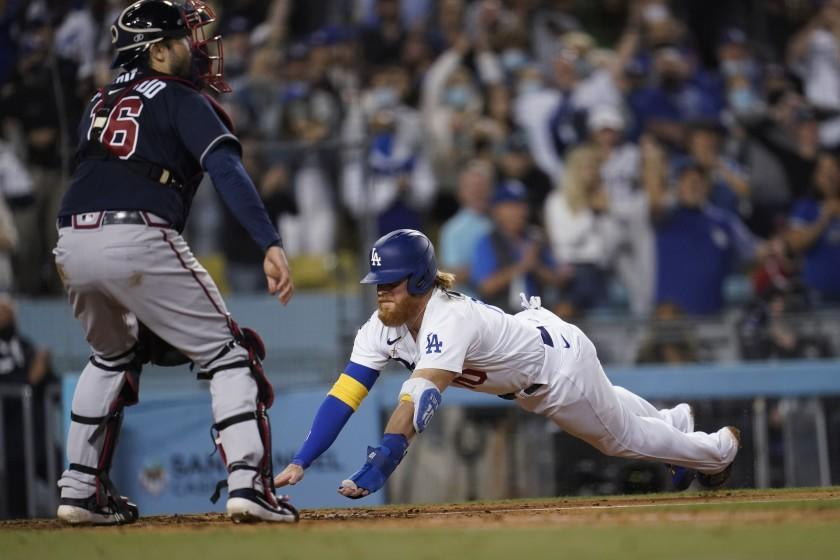 Los Angeles Dodgers' Justin Turner, right, scores past Atlanta Braves catcher Travis d'Arnaud on a single by AJ Pollock during the eighth inning of a baseball game Wednesday, Sept. 1, 2021, in Los Angeles. (AP Photo/Marcio Jose Sanchez)