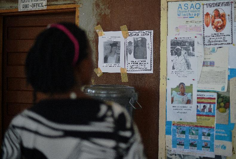 A woman looks at the obituary notices for medical staff who have died from the Ebola virus at the Kenema government hospital in Sierra Leone, August 16, 2014 (AFP Photo/Carl de Souza)