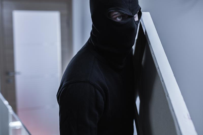 Close-up of robber in balaclava stealing painting