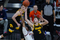 Iowa guard Jordan Bohannon (3) is fouled as he shoots by Illinois guard Andre Curbelo (5) in the first half of an NCAA college basketball game at the Big Ten Conference tournament in Indianapolis, Saturday, March 13, 2021. (AP Photo/Michael Conroy)
