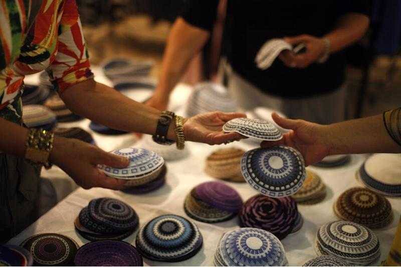 "In this picture taken Saturday, Aug. 21, 2010,  Jewish women buys men's skull caps during a designer fashion fair in Jerusalem. A lawyer representing DC Comics and Marvel says the comics giants are suing a Jerusalem vendor for selling Jewish skullcaps, or kippas, adorned with unauthorized images of crime-fighting superheroes Batman and Spiderman. Lawyer Chagay Netzer said the ""Kippa Man"" store was violating the intellectual property rights of both companies. DC Comics and Marvel are each demanding 25,500 U.S. dollars in damages and expect the store to stop selling the kippas. (AP Photo/Maya Hasson, File)"