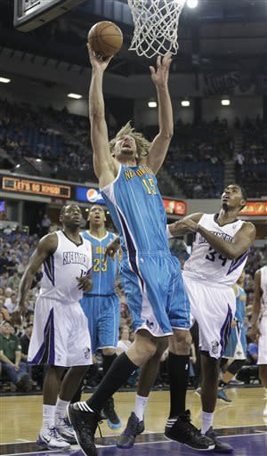 New Orleans Hornets center Robin Lopez, center, goes to the basket between Sacramento Kings' Tyreke Evans, left, and Jason Thompson during the first quarter of an NBA basketball game in Sacramento, Calif., Wednesday, April 10, 2013. (AP Photo/Rich Pedroncelli)