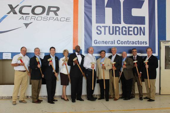 XCOR Aerospace representatives and Midland, Texas officials pose for a photo during a ceremonial wall-breaking event to mark the start of renovations on a hangar at Midland International Airport in Texas, the future home of XCOR's private Lynx