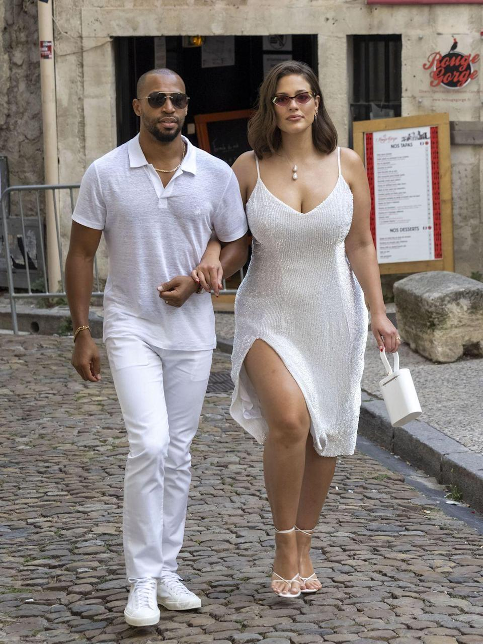 <p>All white and absolutely stunning, Ashley Graham attended Sophie Turner and Joe Jonas' reception dinner in France, along with husband Justin Ervin, in this thigh slit white spaghetti strap dress. </p>