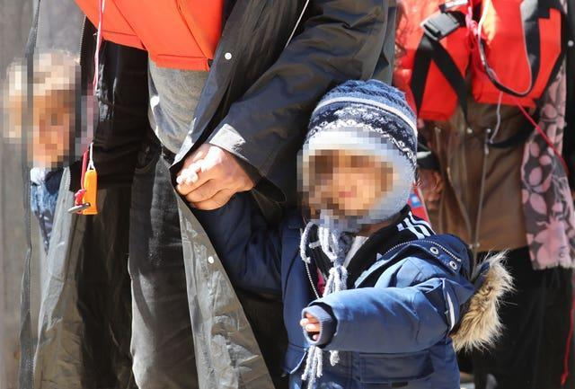 A group of people, including children, are brought in to Dover
