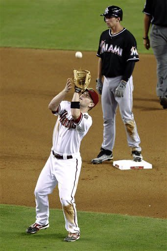 Arizona Diamondbacks' Aaron Hill catches a pop fly hit by Miami Marlins' Ricky Nolasco as Marlins' Rob Brantly stands on second during the fourth inning of a baseball game, Tuesday, Aug. 21, 2012, in Phoenix. (AP Photo/Matt York)