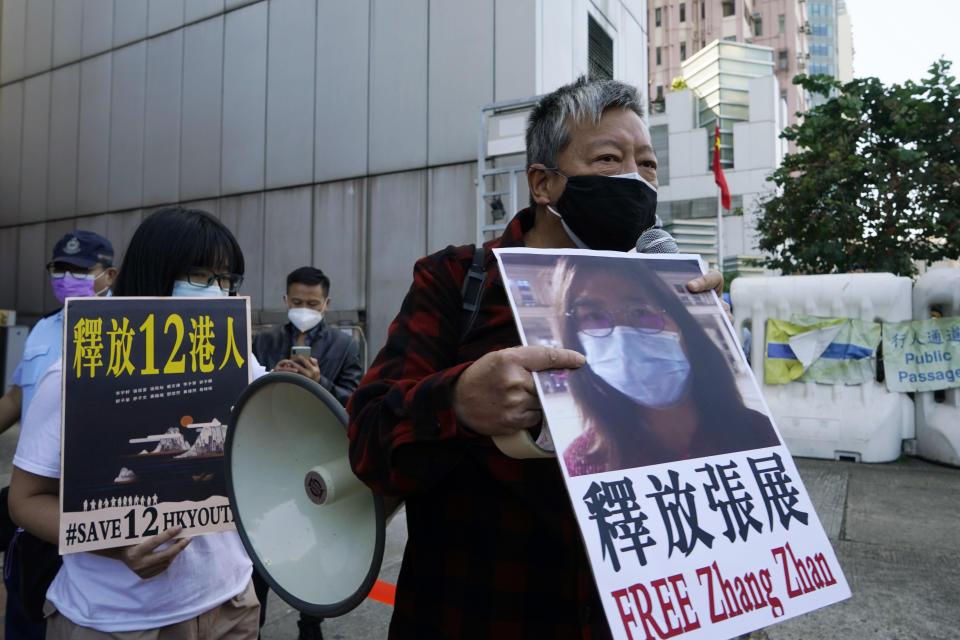 Pro-democracy activists, including Lee Cheuk-Yan, right, hold placards with the picture of Chinese citizen journalist Zhang Zhan as they march to the Chinese central government's liaison office, in Hong Kong, Monday, Dec. 28, 2020. Zhang, a former lawyer and citizen journalist from Shanghai, has been sentenced to four years in prison for her reporting on the initial coronavirus outbreak in Wuhan, China. The activists demanded the releases of Zhang, as well as the 12 Hong Kong activists detained at sea by Chinese authorities. (AP Photo/Kin Cheung)