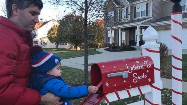 PHOTO: Austin Falli drops off his letter with his daddy holding him up to the mailbox. (Shawna Calvert/Letters to Santa Mail Station)
