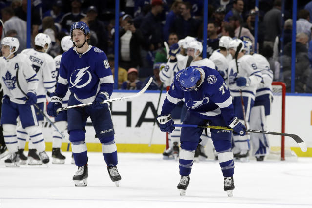 Tampa Bay Lightning center Anthony Cirelli (71) and defenseman Mikhail Sergachev (98) react as the Toronto Maple Leafs celebrate their win over the Lightning during an NHL hockey game Tuesday, Feb. 25, 2020, in Tampa, Fla. (AP Photo/Chris O'Meara)