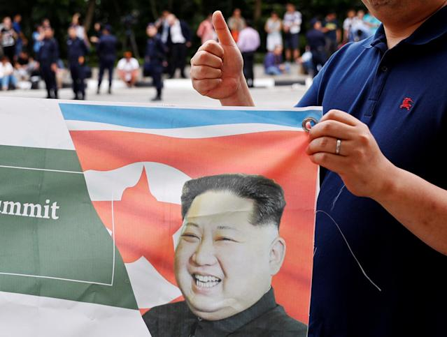 <p>A South Korean man flashes a thumbs-up as he holds up a banner in support of the summit between U.S. President Donald Trump and North Korea's leader Kim Jong Un, near the Capella hotel on Sentosa island in Singapore June 12, 2018. (Photo: Kim Kyung-hoon/Reuters) </p>