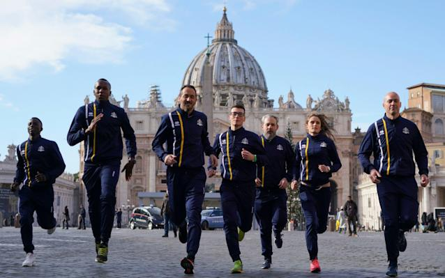 Members of the Vatican's new sports club run in front of St Peter's Basilica - AP