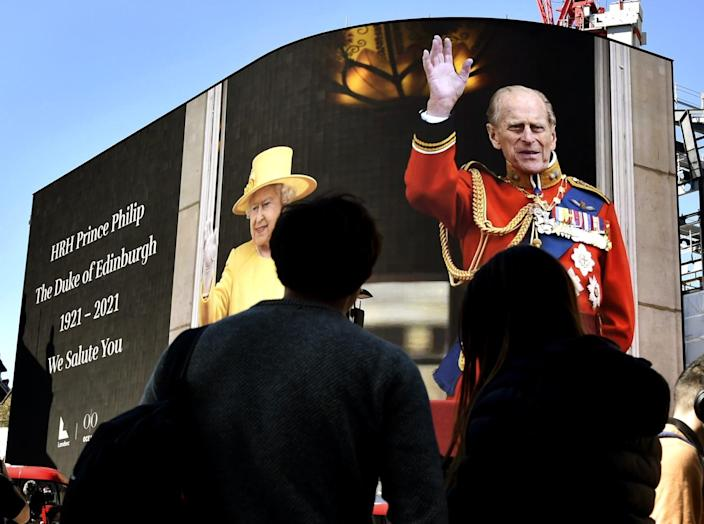 An image of Prince Philip with Queen Elizabeth II is displayed on a giant screen Saturday at Piccadilly Circus in London.
