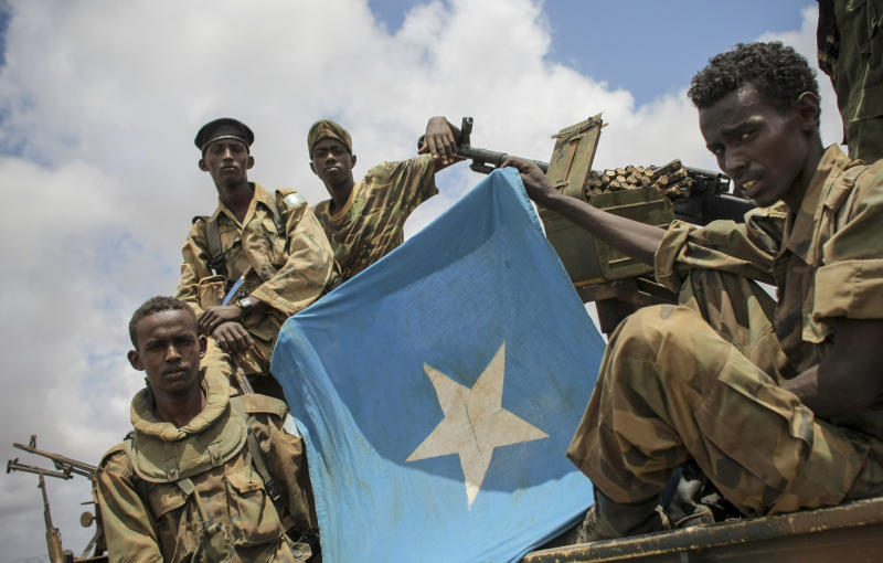 In this photo released by the African Union-United Nations Information Support Team, soldiers of the Somali National Army (SNA) are seen displaying the Somali national flag in Saa'moja, around 7km north-west of the port city of Kismayo, in southern Somalia, Monday, Oct. 1, 2012. Residents in the southern Somali port city of Kismayo say Somali troops have entered the city for the first time since Kenyan troops carried out an amphibious assault on the coastal port city last week, causing al-Shabab militants to flee. (AP Photo/AU-UN IST, Stuart Price)