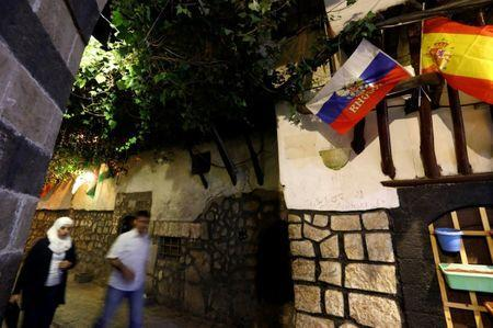 People walk past Russian and Spanish flags in the old town of Damascus, Syria June 19, 2018. Picture taken June 19, 2018. REUTERS/Omar Sanadiki