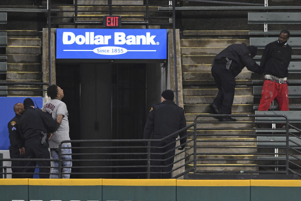 Two people who were apparently unauthorized to be in the stadium grounds are taken into custody by Cleveland police officers during the fifth inning of Game 2 of an American League wild-card baseball series between the New York Yankees and Cleveland Indians, Wednesday, Sept. 30, 2020, in Cleveland. (AP Photo/David Dermer)