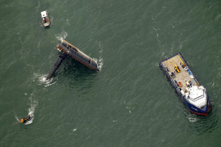 FILE- In this April 18, 2021, file photo, rescue boats are seen next to the capsized lift boat Seacor Power, left, seven miles off the coast of Louisiana in the Gulf of Mexico. The lift boat had lowered its legs and was trying to turn to face heavy winds when it flipped in the Gulf of Mexico off Louisiana last month, according to a preliminary federal report released Tuesday, May 18, 2021. (AP Photo/Gerald Herbert, File)
