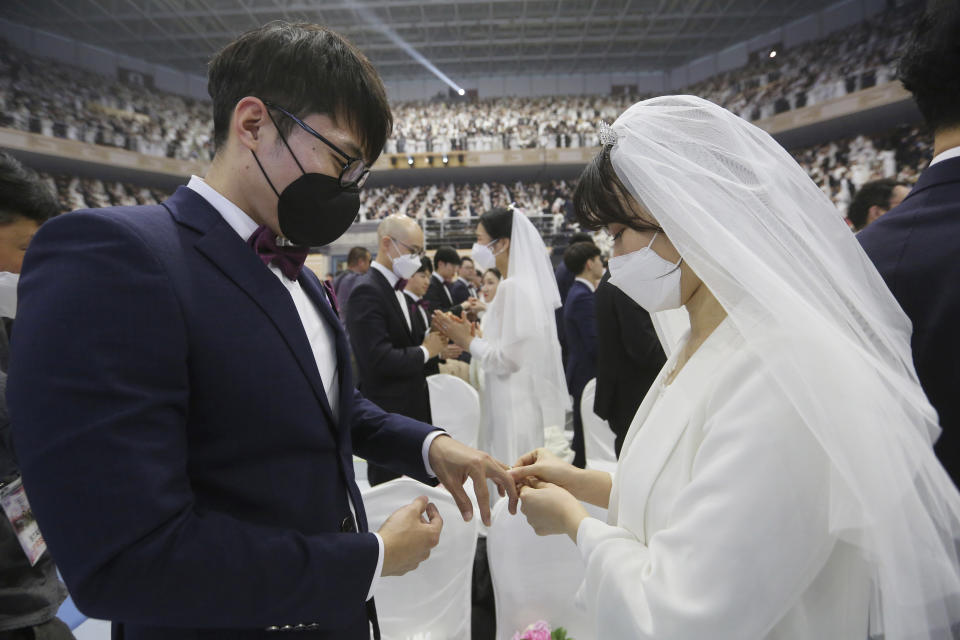 A couple wearing face masks exchanges their rings in a mass wedding ceremony at the Cheong Shim Peace World Center in Gapyeong, South Korea, Friday, Feb. 7, 2020. (AP Photo/Ahn Young-joon)