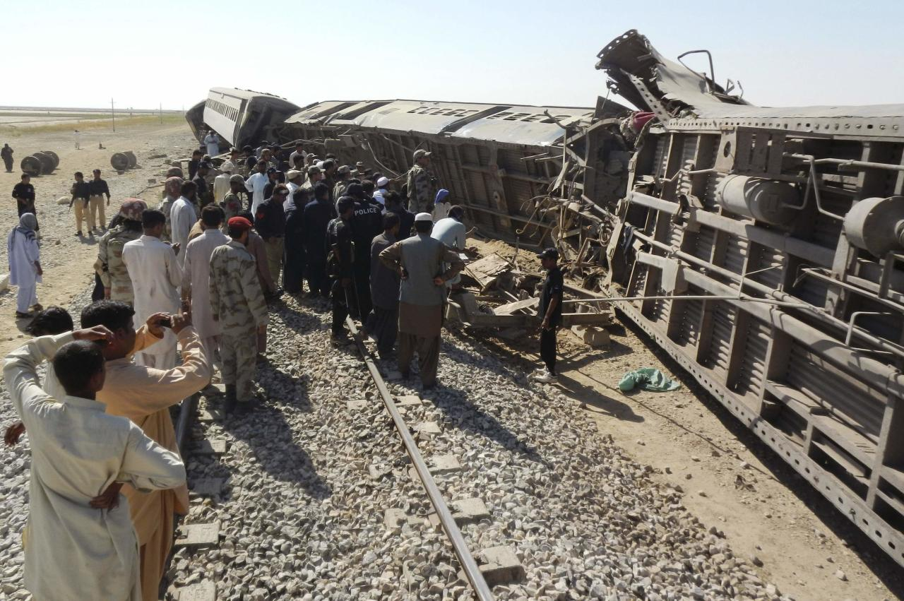 Officials, rescue workers and residents gather near the passenger train derailed after it was hit by a bomb attack in Dera Murad Jamali, located in the Nasirabad District of Balochistan province, October 21, 2013. At least five passengers were killed and 16 wounded when the train was bombed and derailed in restive southwest Pakistan on Monday, officials said. REUTERS/Amir Hussain (PAKISTAN - Tags: TRANSPORT DISASTER CRIME LAW TPX IMAGES OF THE DAY)