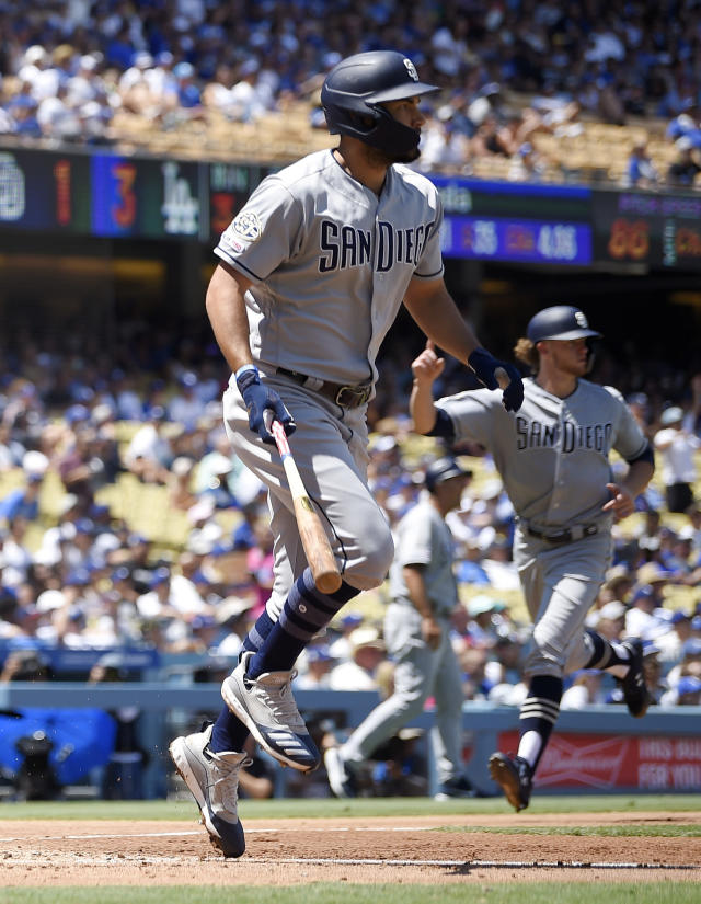 San Diego Padres' Eric Hosmer, left, runs toward first after hitting a grand slam while Chris Paddack, back right, scores during the third inning of a baseball game against the Los Angeles Dodgers, Sunday, Aug. 4, 2019, in Los Angeles. (AP Photo/Mark J. Terrill)