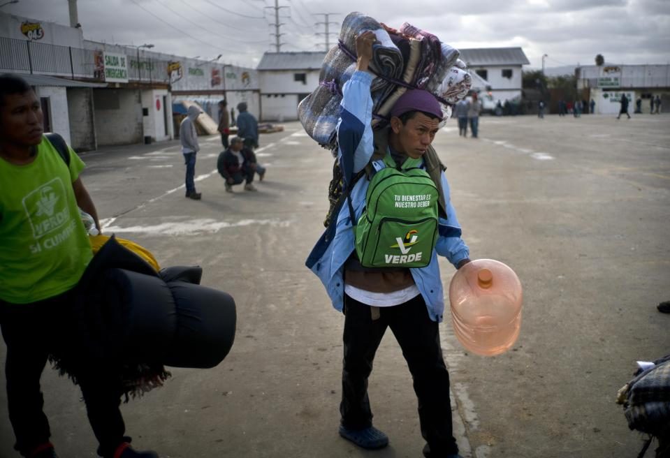 Honduran migrants arrive at a new shelter, in Tijuana, Mexico, Friday, Nov. 30, 2018. A group of migrants boarded buses at an overcrowded sports complex within view of the border late Thursday and early Friday to a new site, an events hall a little further away. (AP Photo/Ramon Espinosa)